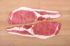 Raw bacon slices on a wooden cutting board. Stock Photo