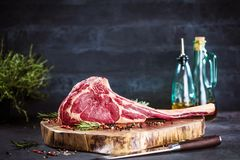 Barbecue Tomahawk Steak on dark background with herb prepared for grill. Raw Barbecue Tomahawk Steak on a wood and dark background with rosmarin stock photography
