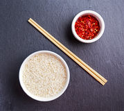 Raw basmati rice in a bowl with chillie flakes and Bamboo chopsticks on stone table.  Stock Photo