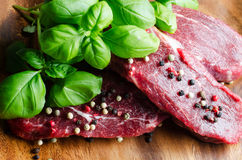 Raw beef. Basil and pepper on wooden cutting board Stock Image