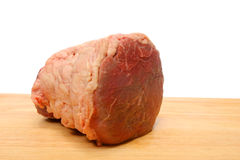 Raw beef. A joint of raw beef on a wooden board Royalty Free Stock Photos