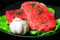 Raw beef on black plate. Raw beef steak with black pepper and garlic on the  leaf of lettuce Royalty Free Stock Image