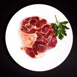 Raw beef with bone on white plate Stock Photo