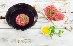 Raw beef burger patty on iron pan. Stock Photography