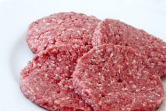 Raw beef burgers. Against white background Royalty Free Stock Images