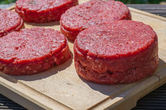 Raw beef burgers close up on a chopping board Royalty Free Stock Image