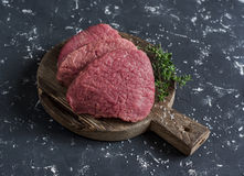 Raw beef chops and fresh thyme on a wooden cutting board. On a dark background Stock Photo