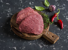 Raw beef chops on a wooden cutting board Royalty Free Stock Photo