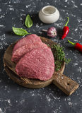 Raw beef chops on a wooden cutting board. On a dark background Stock Images