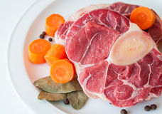 Raw beef closeup. Closeup of raw beef shin with carrots and laurel leaves Stock Photos