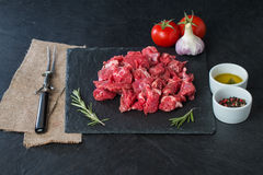 Raw beef cubes. With rosemary and beefsteak spices on black background Stock Photography