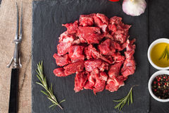 Raw beef cubes. With rosemary and beefsteak spices on black background Royalty Free Stock Photo