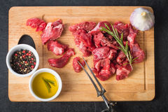 Raw beef cubes. With rosemary and beefsteak spices on wooden cutting Board Royalty Free Stock Images