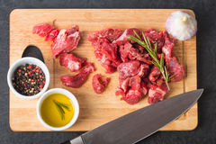 Raw beef cubes. With rosemary and beefsteak spices on wooden cutting Board Royalty Free Stock Photos