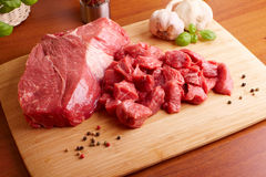 Raw beef on cutting board. Fresh raw beef on wooden cutting board with garlic, pepper and basil Royalty Free Stock Photography