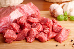 Raw beef on cutting board. Fresh raw beef on wooden cutting board with garlic, pepper and basil Royalty Free Stock Image