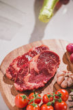 Raw beef on a cutting board with spices and ingredients for coo Stock Image