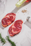 Raw beef on a cutting board  with spices and ingredients for coo. King Royalty Free Stock Photo