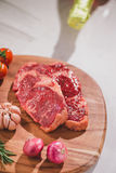 Raw beef on a cutting board  with spices and ingredients for coo. King Royalty Free Stock Image