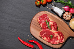 Raw beef on a cutting board  with spices and ingredients for coo. King Royalty Free Stock Photos