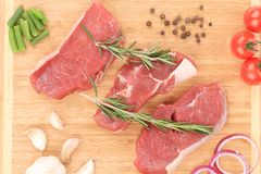 Raw beef on cutting board and vegetables. Stock Image