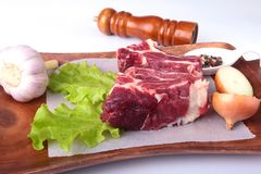 Raw beef edges, lettuce leaf, garlic, pepper grinder and spices on wooden desk isolated on white background from above. And copy space. ready for cooking Royalty Free Stock Image