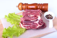 Raw beef edges, lettuce leaf, pepper grinder and spices on wooden desk isolated on white background from above and copy Stock Images