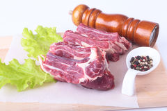 Raw beef edges, lettuce leaf, pepper grinder and spices on wooden desk isolated on white background from above and copy Stock Photo