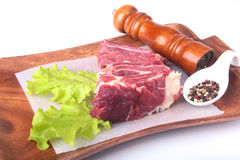 Raw beef edges, lettuce leaf, pepper grinder and spices on wooden desk isolated on white background from above and copy Royalty Free Stock Photos