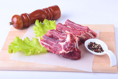 Raw beef edges, lettuce leaf, pepper grinder and spices on wooden desk isolated on white background from above and copy Royalty Free Stock Photo