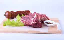 Raw beef edges, lettuce leaf, pepper grinder and spices on wooden desk isolated on white background from above and copy Stock Photography