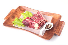 Raw beef edges, lettuce leaf and spices on wooden desk isolated on white background from above and copy space. ready for Royalty Free Stock Images