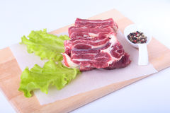 Raw beef edges, lettuce leaf and spices on wooden desk isolated on white background from above and copy space. ready for Stock Photography