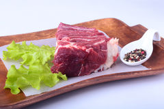 Raw beef edges, lettuce leaf and spices on wooden desk isolated on white background from above and copy space. ready for Stock Photo