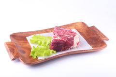 Raw beef edges and lettuce leaf on wooden desk isolated on white background from above and copy space. ready for cooking Stock Photo
