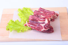 Raw beef edges and lettuce leaf on wooden desk isolated on white background from above and copy space. ready for cooking Royalty Free Stock Photography