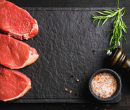 Raw beef Eye Round steaks with spices, rosemary. Copy space. Raw beef Eye Round steaks with spices and rosemary on black slate stone board over dark wooden Royalty Free Stock Images