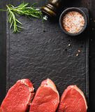 Raw beef Eye Round steaks with spices, rosemary. Copy space. Raw beef Eye Round steaks with spices and rosemary on black slate stone board over dark wooden Stock Images