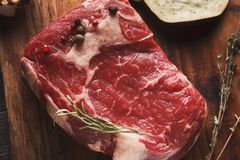 Raw beef filet mignon steak on wooden board. Raw filet mignon. Fresh beef meat with rosemary on wooden board, kitchen background. Organic ingredients for royalty free stock photos