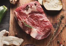 Raw beef filet mignon steak on wooden board. Raw filet mignon. Fresh beef meat with rosemary on wooden board, kitchen background. Organic ingredients for stock photos