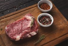 Raw beef filet mignon steak on wooden board. Raw filet mignon. Fresh beef meat, spices and herbs on wooden board, kitchen background. Organic ingredients for Royalty Free Stock Photography