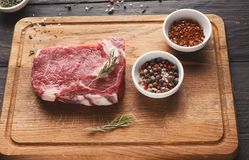 Raw beef filet mignon steak on wooden board. Raw filet mignon. Fresh beef meat, spices and herbs on wooden board, kitchen background. Organic ingredients for royalty free stock image