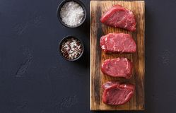 Raw beef filet mignon steaks with spices on wooden board at blac. Raw filet mignon steaks with spices closeup. Slices of fresh beef meat arranged in a row on stock photography