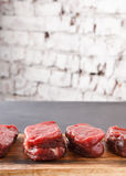 Raw beef filet mignon steaks on wooden board at black background against brick wall. Raw filet mignon steaks closeup. Slices of fresh beef meat arranged in a row royalty free stock images