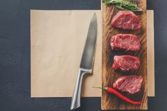 Raw beef filet mignon steaks on wooden board and craft papper. Raw filet mignon steaks. Fresh beef meat, rosemary and chilli on wooden board on craft paper at Royalty Free Stock Photos