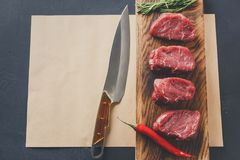 Raw beef filet mignon steaks on wooden board and craft papper. Raw filet mignon steaks. Fresh beef meat, rosemary and chilli on wooden board on craft paper at Royalty Free Stock Photo