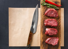 Raw beef filet mignon steaks on wooden board and craft papper. Raw filet mignon steaks. Fresh beef meat, rosemary and chilli on wooden board on craft paper at Stock Image