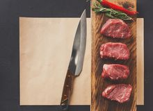 Raw beef filet mignon steaks on wooden board and craft papper. Raw filet mignon steaks. Fresh beef meat, rosemary and chilli on wooden board on craft paper at Stock Photography