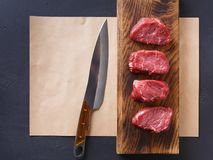 Raw beef filet mignon steaks on wooden board and craft papper. Raw filet mignon steaks. Fresh beef meat on wooden board and craft paper at back background royalty free stock image