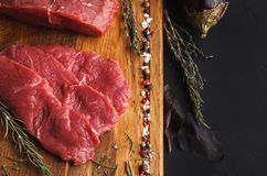 Raw beef filet mignon steaks on wooden board. Raw filet mignon steaks. Fresh beef meat, rosemary on wooden board at black background. Organic ingredients for Stock Photography